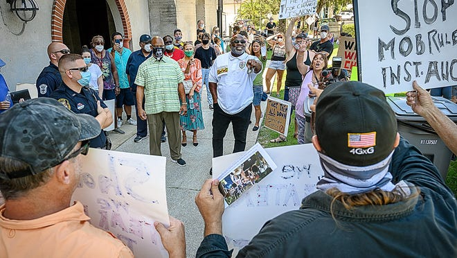 St. Augustine Police officers keep opposing protesters separated outside of St. Augustine's City Hall in the Lightner building downtown as the City Commission hears public comment on removing a memorial honoring Confederate soldiers from the Plaza de la Constitucion on Monday.