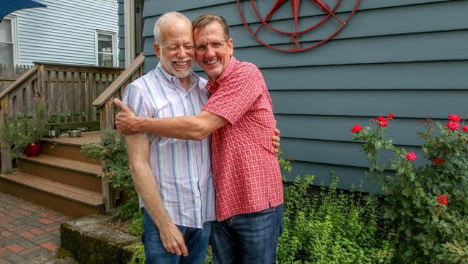 Paul Schierenbeck, left, and David Mann in the backyard of their Pawtucket home, where they were wed.
