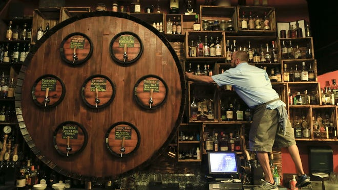 The barrel facade behind the bar houses the taps dispensing whiskey, cognac and other spirits at Radiator Whiskey at Pike Place Market. The shop also serves comfort food.