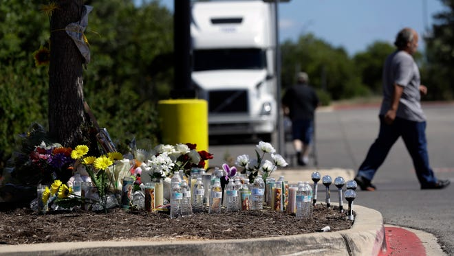 A man leaves a make-shift memorial in the parking lot of a Walmart store near the site where authorities discovered a tractor-trailer packed with immigrants on July 26, 2017, in San Antonio.