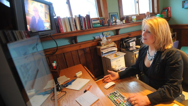 Psychiatrist Jenna Saul talks with staff at another clinic about shared patients via webcam.