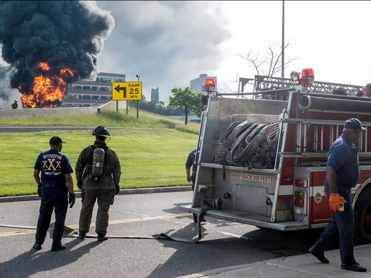 Detroit firefighters watch as a gasoline tanker burns Sunday on an overpass ramp on I-75.