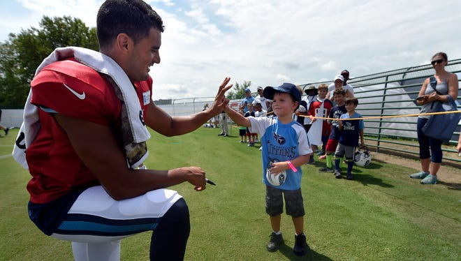 Titans quarterback Marcus Mariota (8) gets a high-five from Carter McBroom 4, after practice at St. Thomas Sports Park Tuesday Aug. 2, 2016, in Nashville, Tenn.