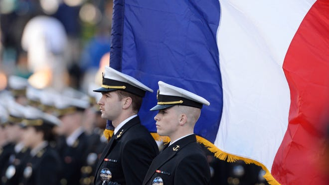 Navy Midshipmen color company holds an French Flag at attention during the pregame march.