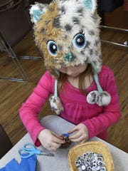 Wearing her owl hat, Reaghan Buchner of Baileys Harbor puts together a pine cone owl with button eyes in the craft area at last year's Owl-O-Rama..