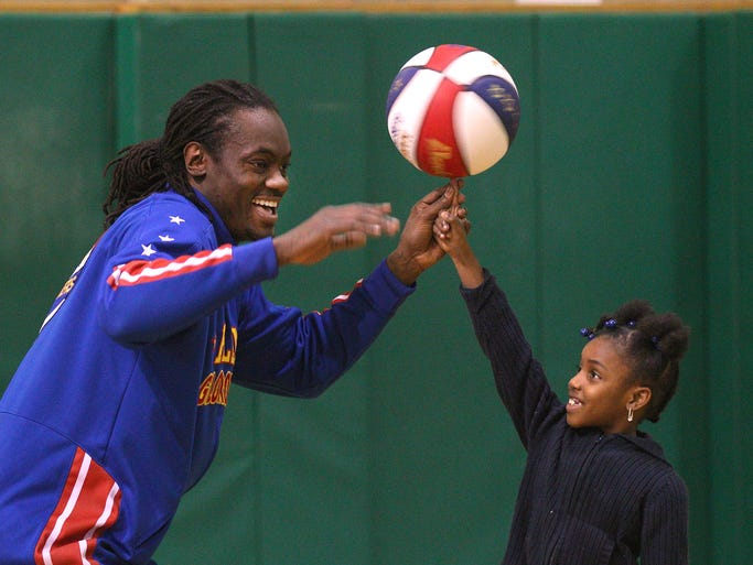 Slick Willie Shaw, of the Harlem Globetrotters has some fun with Sy'Asia Mason, a 2nd grader at School 20 during a visit.