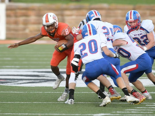 Mansfield Senior's Angelo Grose looks to avoid a pack of West Holmes tacklers Friday night at Arlin Field.