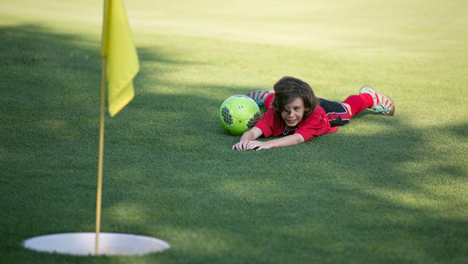 Jacob Hill, 12, of Canandaigua, lies on the green during a round of foot golf.