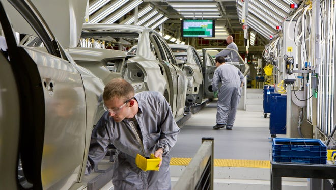 Paint shop workers attend to Volkswagen Passat sedans at the German automaker's plant in Chattanooga, Tenn., in  2012.