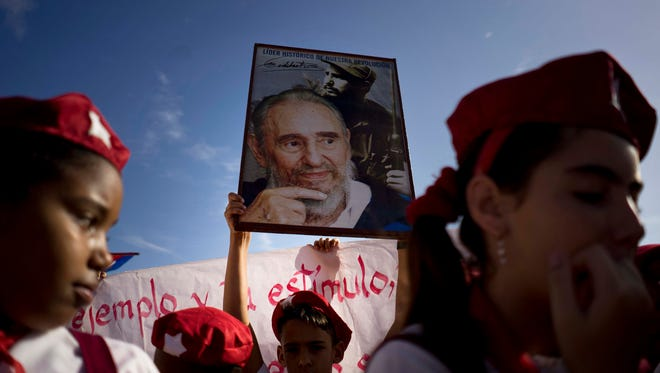 A boy holds up a photo of Cuban former President Fidel Castro during a parade marking the 163rd anniversary of the birth of Cuba's national independence hero Jose Marti, in Regla, Cuba, Thursday, Jan. 28, 2016. Through his writings and political activity, Marti became a symbol for Cuba's bid for independence against Spain in the 19th century. (AP Photo/Ramon Espinosa)