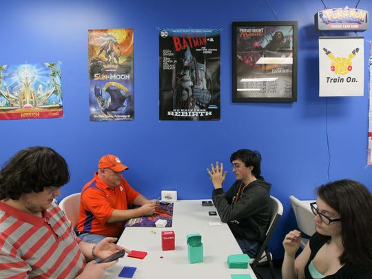 Justin Brown, from left, of Honea Path, Jody Lusk of Seneca, Nick Burger of Honea Path, and Elana Bagwell of Honea Path play Yu-Gi-Oh! on Saturday at Planet Comics in Anderson.