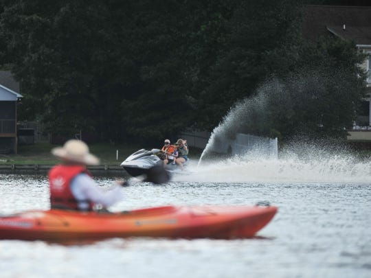 A wave runner with three passengers passes by kayakers