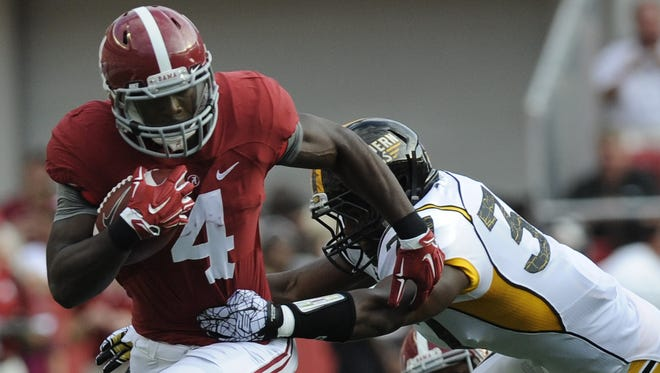 Alabama running back T.J. Yeldon (4) tries to shake Southern Miss linebacker Alan Howze (37) at Bryant Denny Stadium in Tuscaloosa, Ala. on Saturday September 13,  2014.