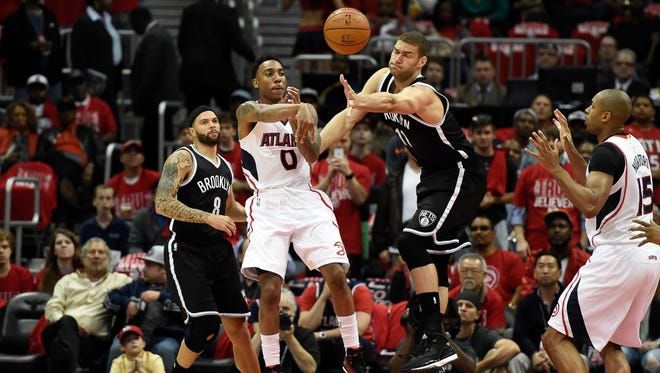 Jeff Teague passes the ball past  Nets center Brook Lopez.