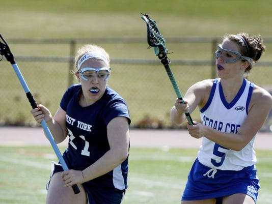 West York's Sara Wood, left, tries to get around Cedar Crest's Kayla Sanger during a girls' lacrosse game at in Lebanon on April 11. Although West York lost to Cedar Crest, 15-13, the Bulldogs held an 8-4 overall record and 4-3 mark in the YAIAA entering this week.