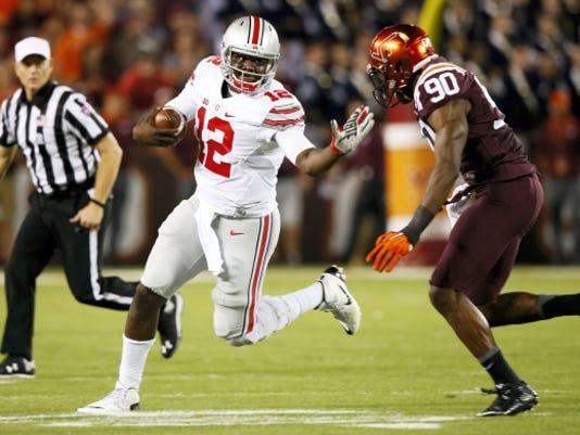 Ohio State quarterback Cardale Jones (12) tries to get past Virginia Tech defensive end Dadi Lhomme Nicolas (90) during the first half of Monday's game in Blacksburg, Va. Ohio State won, 42-24.