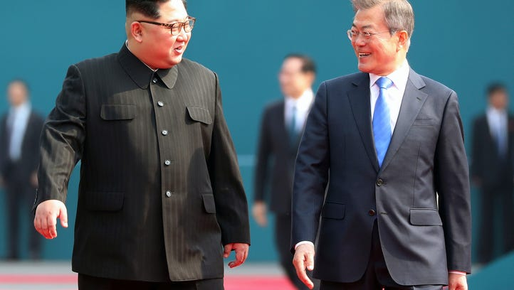 North Korean leader Kim Jong Un (left) talks with South