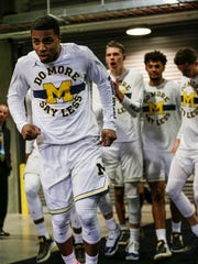 Michigan guard Jaaron Simmons, left, takes the floor at INTRUST Bank Arena on Thursday.