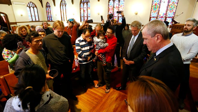 New Jersey Governor Phil Murphy, r,  bows his head as Harry Pangemanan, l, says a prayer in his native Indonesian at the Highland Park Reformed Church. Pangemanan claimed sanctuary this morning after ICE agents went to his front door. January 25, 2018. Highland Park, NJ.