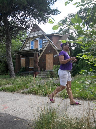 A woman walks by this blighted house on Woodingham, one of the slated homes of the Fitzgerald neighborhood revitalization project Thursday, July 5, 2018.