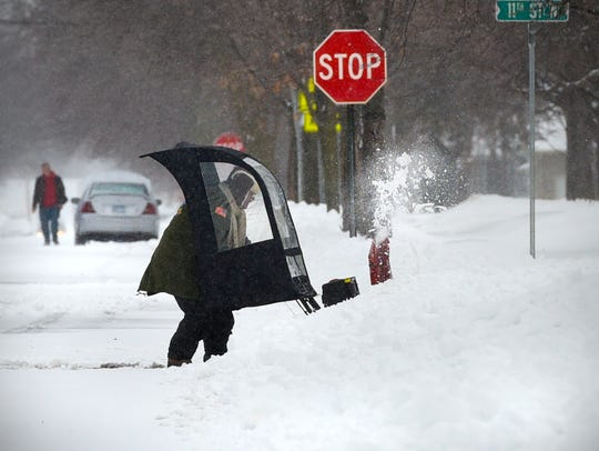 Snowblowers and shovels dotted St. Cloud Monday, March