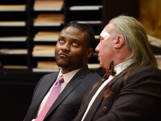 Defendant Courtney Simpson (L) looks upward as he sits