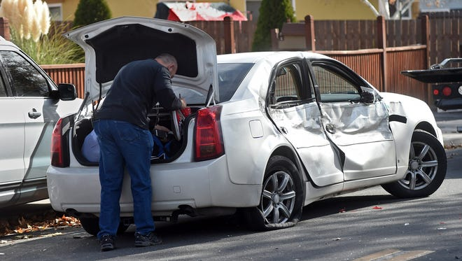 A US Marshal searches a car involved a car crash at Greenbrae Drive and 11th Street where an arrest was made in Sparks on Nov. 21, 2017.