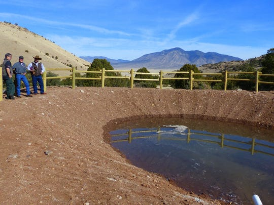 Larry Cordova, Mark Cadwallader and Omar Barnes survey the finished dirt tank for wildlife.