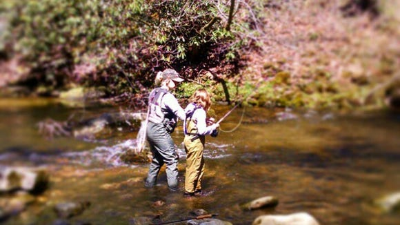 Alleigh Raymond guides a younger child in a fly-fishing lesson. Buncombe County Parks and Recreation and N.C. Wildlife Resources Commission host a Kids Fishing Derby April 29.