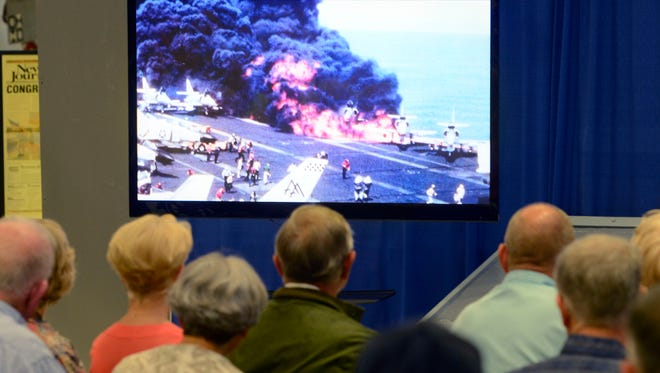 The crowd watches footage of the fire aboard the USS Forrestal in 1967 during the 50th anniversary commemoration ceremony at the National Naval Aviation Museum Saturday, July 29, 2017.