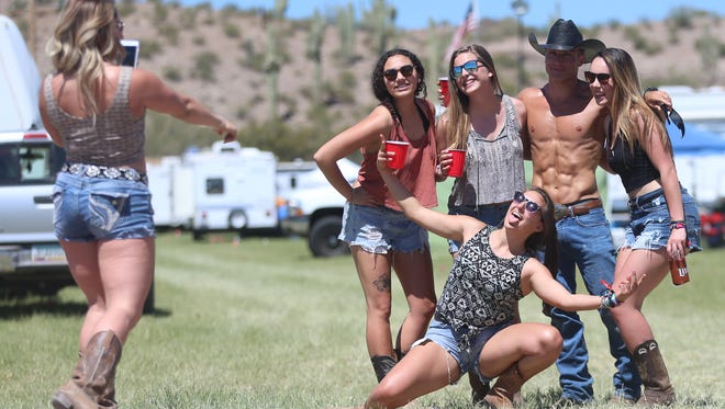 "Women pose for a picture with the ""buff cowboy"" at the campgrounds at Country Thunder in Florence, Ariz. on April 6, 2017."