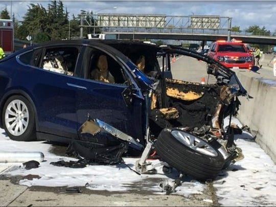 In this Friday March 23, 2018 photo provided by KTVU, emergency personnel work a the scene where a Tesla electric SUV crashed into a barrier on U.S. Highway 101 in Mountain View, Calif.