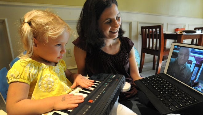Diane Libro talks to her husband, U.S. Air Force Maj. Joey Libro, via Skype while their daughter Catherine plays keyboards for her dad. Joey Libro is deployed to the Phillippines until October and will miss Father's Day with his family.