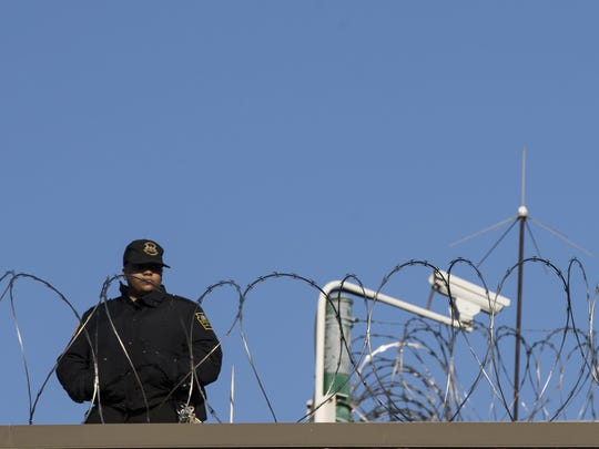 FILE - In this Nov. 27, 2017 file photo, a guard stands watch at the State Correctional Institution in Chester, Pa. As officials consider releasing some inmates to lessen the impact of COVID-19 on Pennsylvania prisons, county prosecutors are telling lawmakers that passing legislation to address that would avoid leaving those decisions to the governor alone. (AP Photo/Matt Rourke, File)