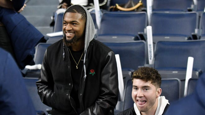 Ole Miss football players Deontay Anderson, left, and Shea Patterson react after entering the arena before Michigan's men's basketball game against UCLA on Saturday at Crisler Center in Ann Arbor. Patterson announced Monday he's transferring to Michigan.