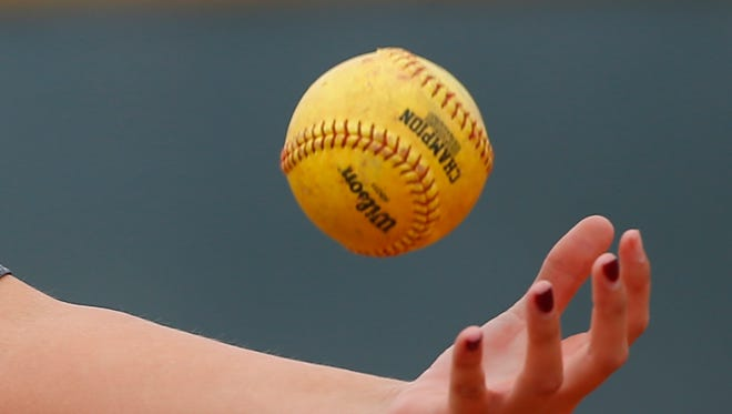 A high school softball is tossed in the air.