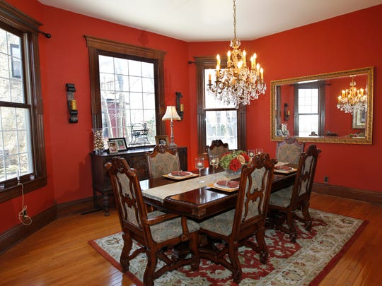 The Youngs' formal dining room, with its large, picturesque windows, is painted a bright shade of red.