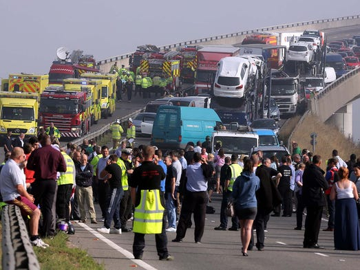 Emergency workers help victims at the scene of a 100-vehicle crash on the freeway at the Sheppey Bridge Crossing on Sept. 5, 2013, near Sheerness, England. Eight people were seriously injured when the vehicles crashed in heavy fog.