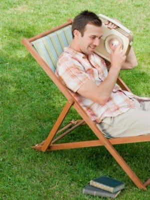 Man relaxing in lawn chair with old-fashioned radio