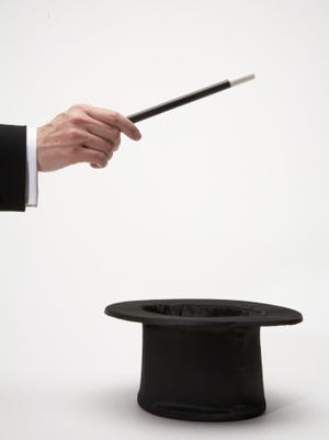 Man holding magic wand over top hat
