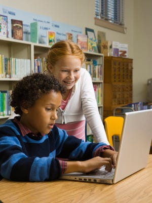 Boy and girl in library with laptop computer