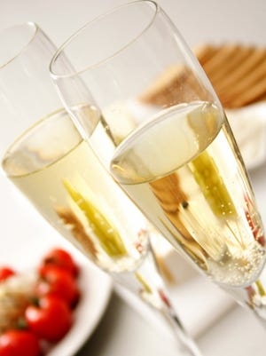 A stock image of sparkling wine with an appetizer.