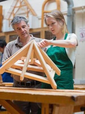 Teacher helping a student to construct a frame.