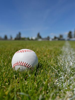 Baseball sitting in grass