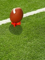 Football atop tee on football field, elevated view