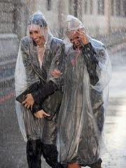 Businesswomen in ponchos walking in rainy street