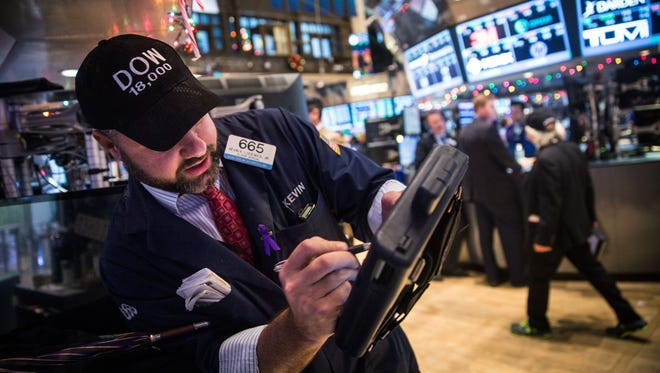 """Traders wear hats that say """"DOW 18,000"""" as they work on the floor of the New York Stock Exchange on Tuesday afternoon."""