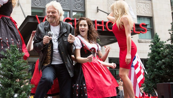 CHICAGO, IL - APRIL 16:  (L) Richard Branson introduces new parental leave for some employees. Here, he celebrates the grand opening of Virgin Hotels Chicago by recreating the iconic parade scene from Ferris Bueller's Day Off on April 16, 2015 in Chicago, Illinois.  (Photo by Jeff Schear/Getty Images for Virgin Hotel) ORG XMIT: 548680249 ORIG FILE ID: 469955604