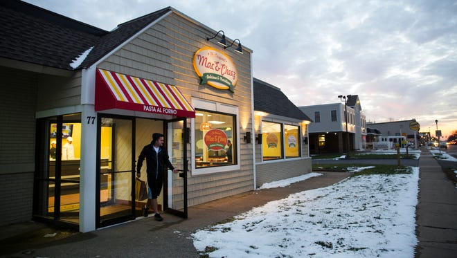 A customer walks out of The Original Mac & Cheez Shop in Webster with a to-go order.
