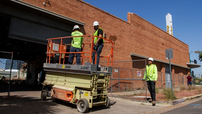 Demolition workers drive a lift into the historic Circles building on Friday, April 15, 2016, in Phoenix. The building was once home to an auto-dealership and a record store.